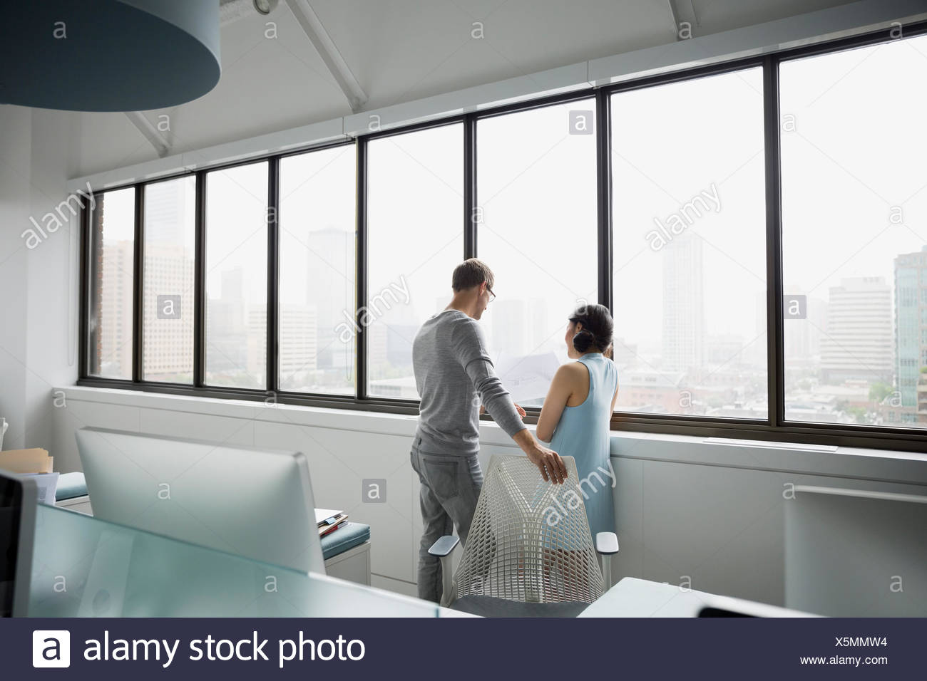 Architects looking out office window - Stock Image