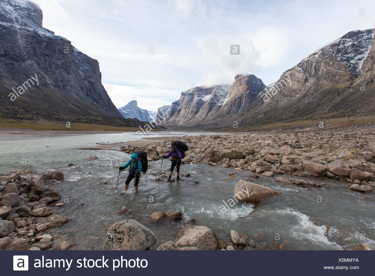 Hikers cross a creek in Auyuittuq National Park, Nunavut, Canada - Stock Image