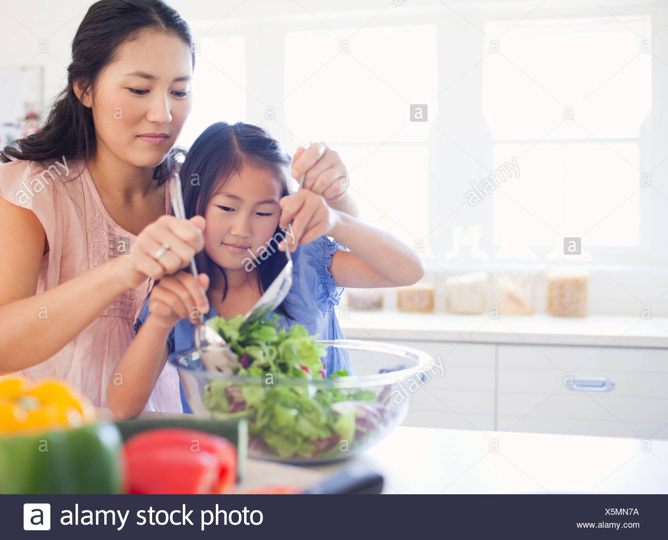 A mother and daughter toss a salad together - Stock Image