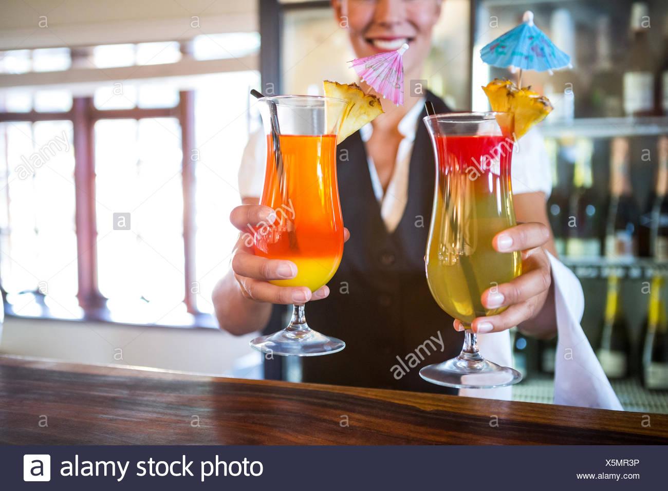 Waitress handing over cocktails - Stock Image