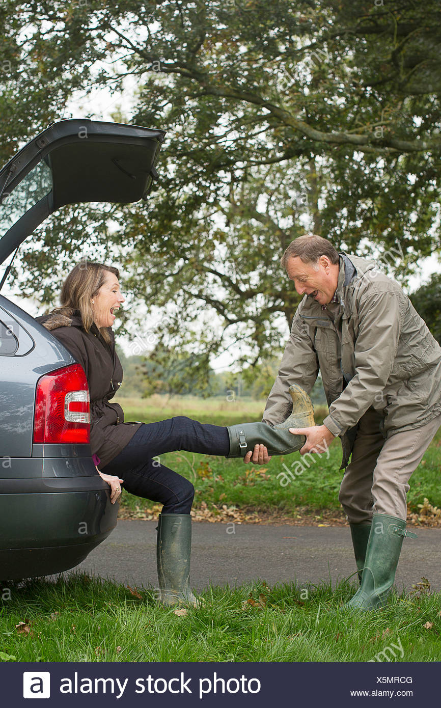 Senior couple taking off boots whilst out - Stock Image