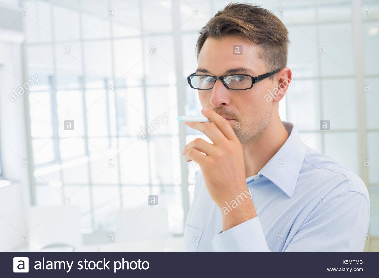 Casual businessman smoking an electronic cigarette - Stock Image