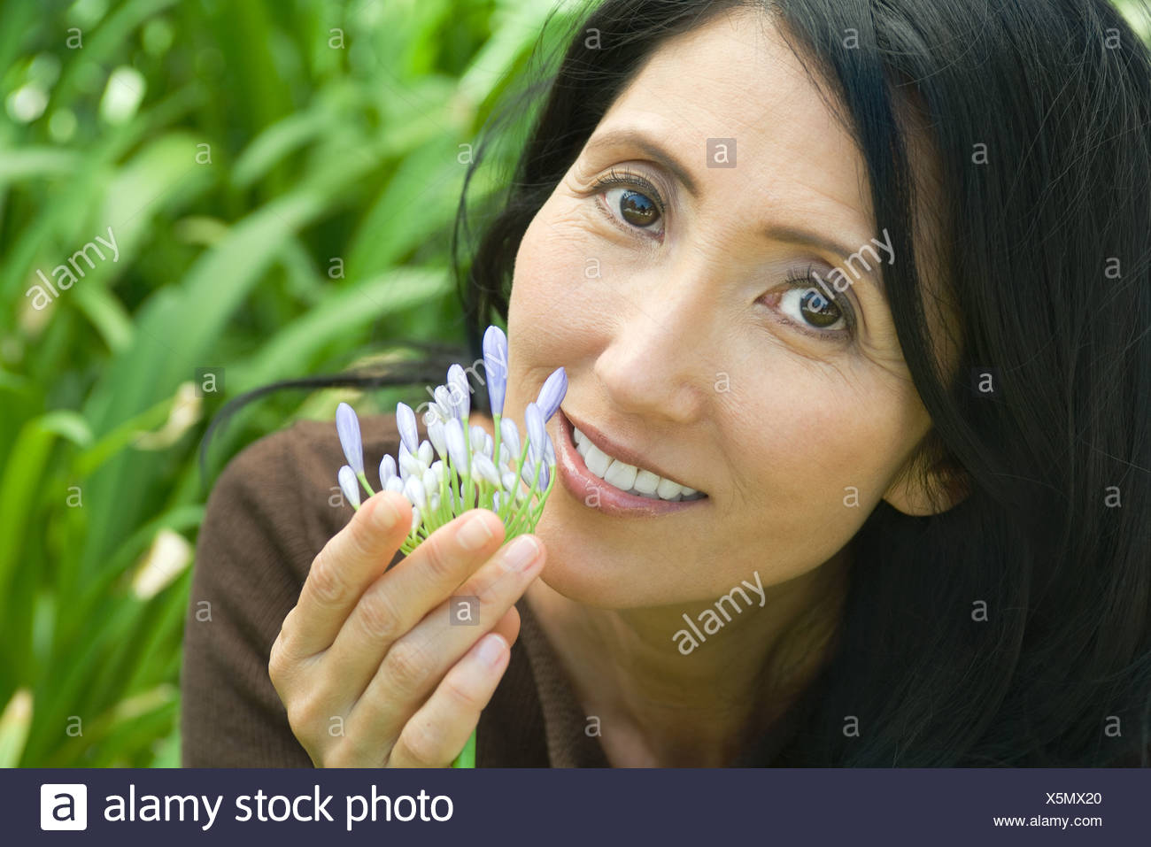 Mature woman smelling flower, smiling at camera, close-up - Stock Image
