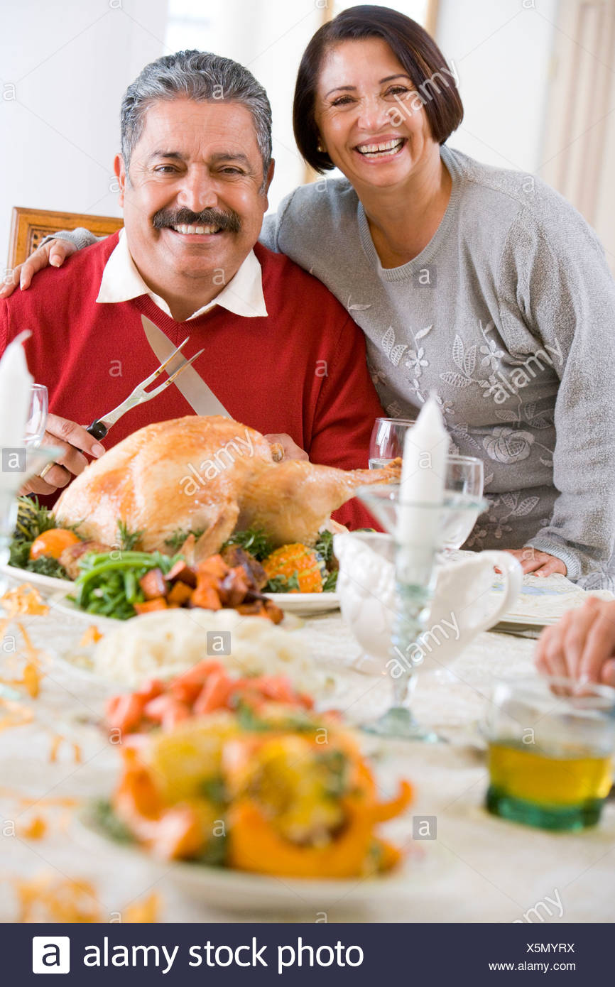 Woman With Her Arm Around Her Husband, Who Is Getting Ready To Carve A Turkey - Stock Image