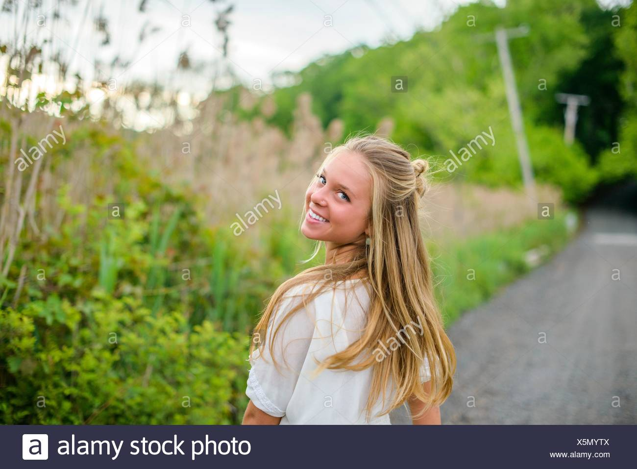 Portrait of young woman with long blond hair looking back on rural road - Stock Image