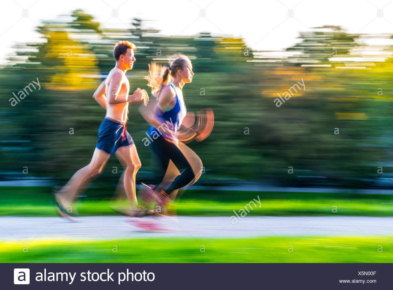 Panning shot, young woman and young man in sportswear jogging through park, Munich, Upper Bavaria, Bavaria, Germany - Stock Image