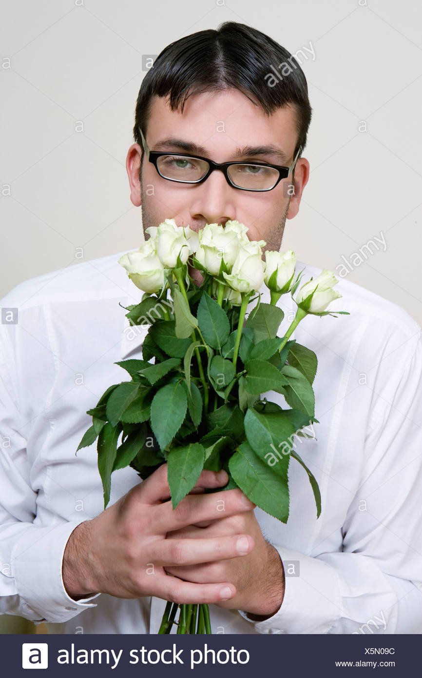 Stupid looking young man with bunch flowers - Stock Image