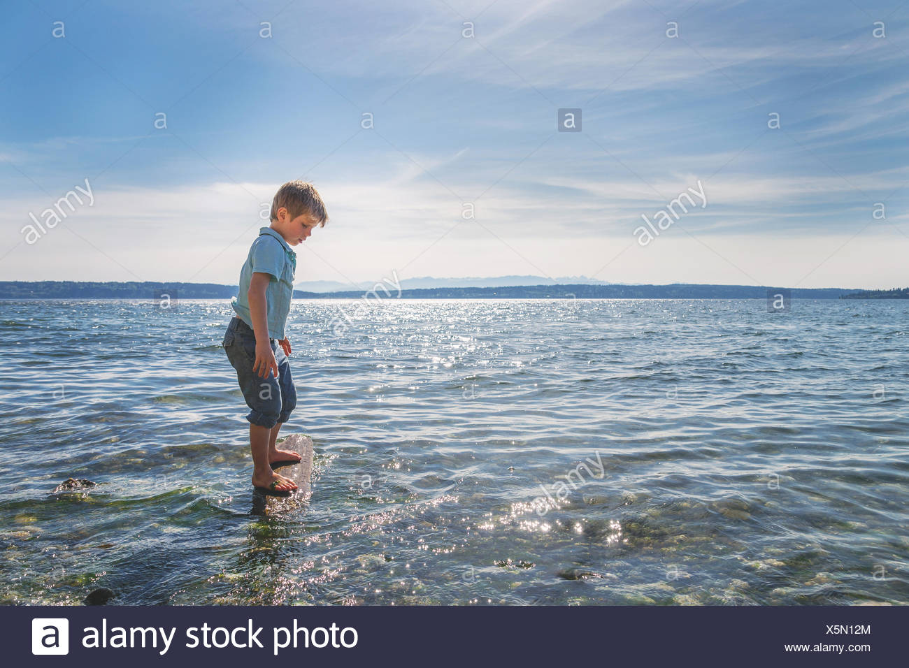 Boy standing on a wooden log in the sea Stock Photo