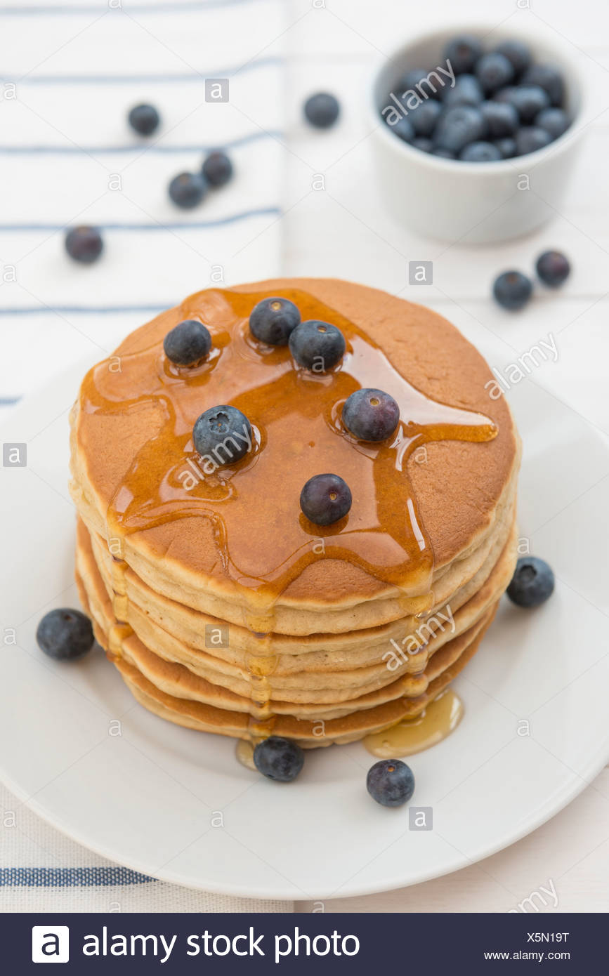 Pancakes, blueberries and honey. - Stock Image