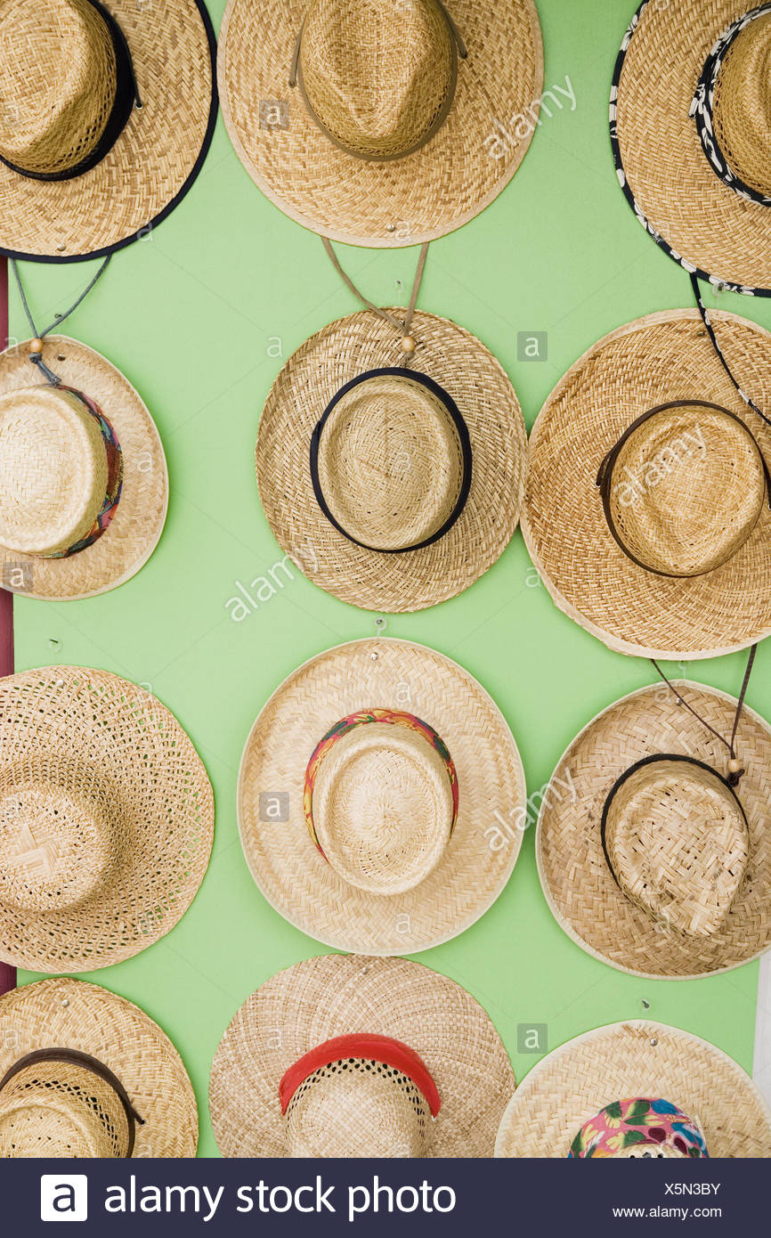 576a33f3b61 Close-up of straw boater hats hanging on the wall - Stock Image