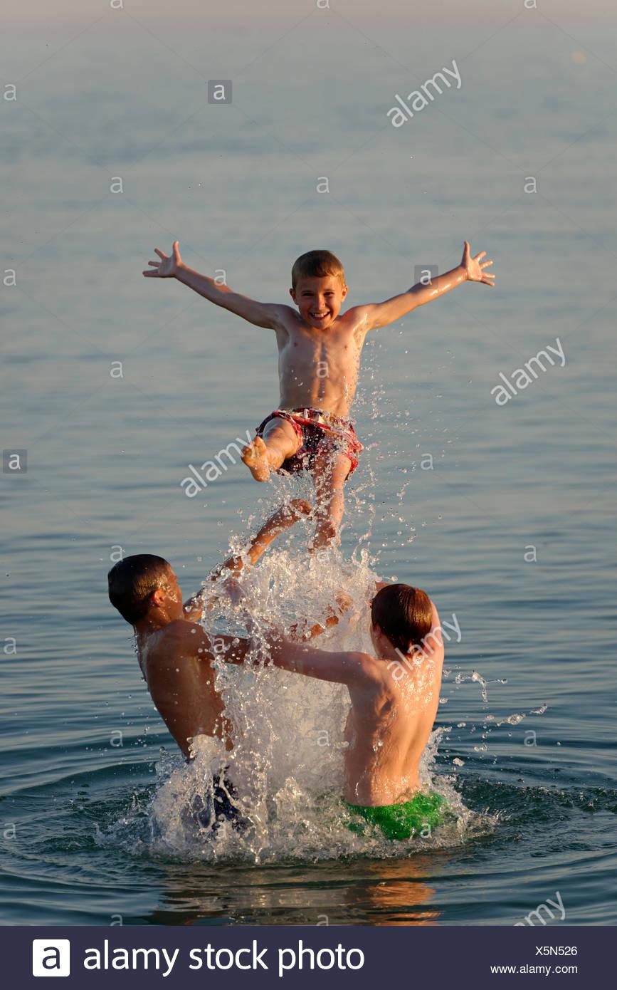 Italy, three teenage boys having fun at seaside - Stock Image
