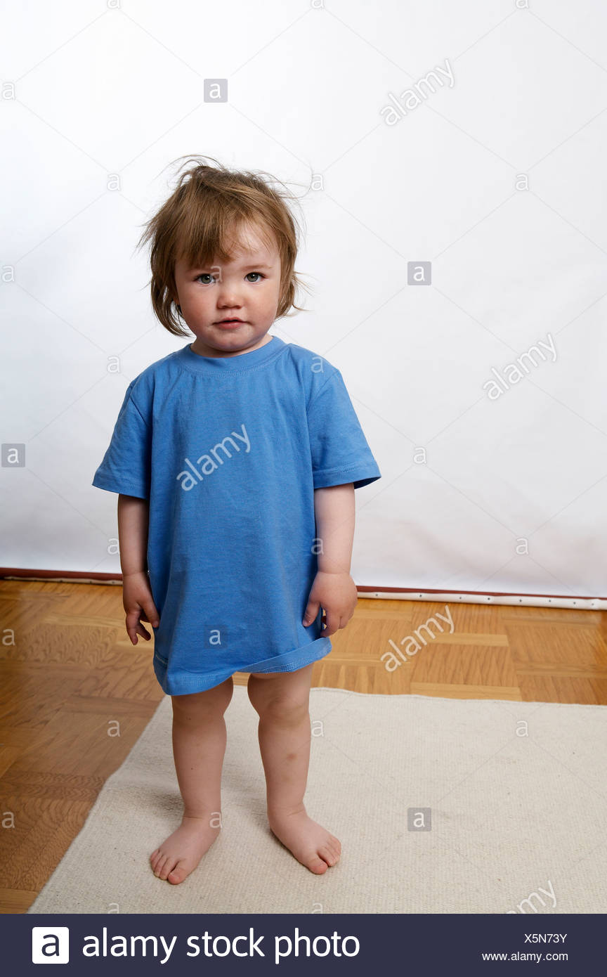 Portrait of girl with tousled hair and in blue t-shirt standing with bare feet on rug at home - Stock Image