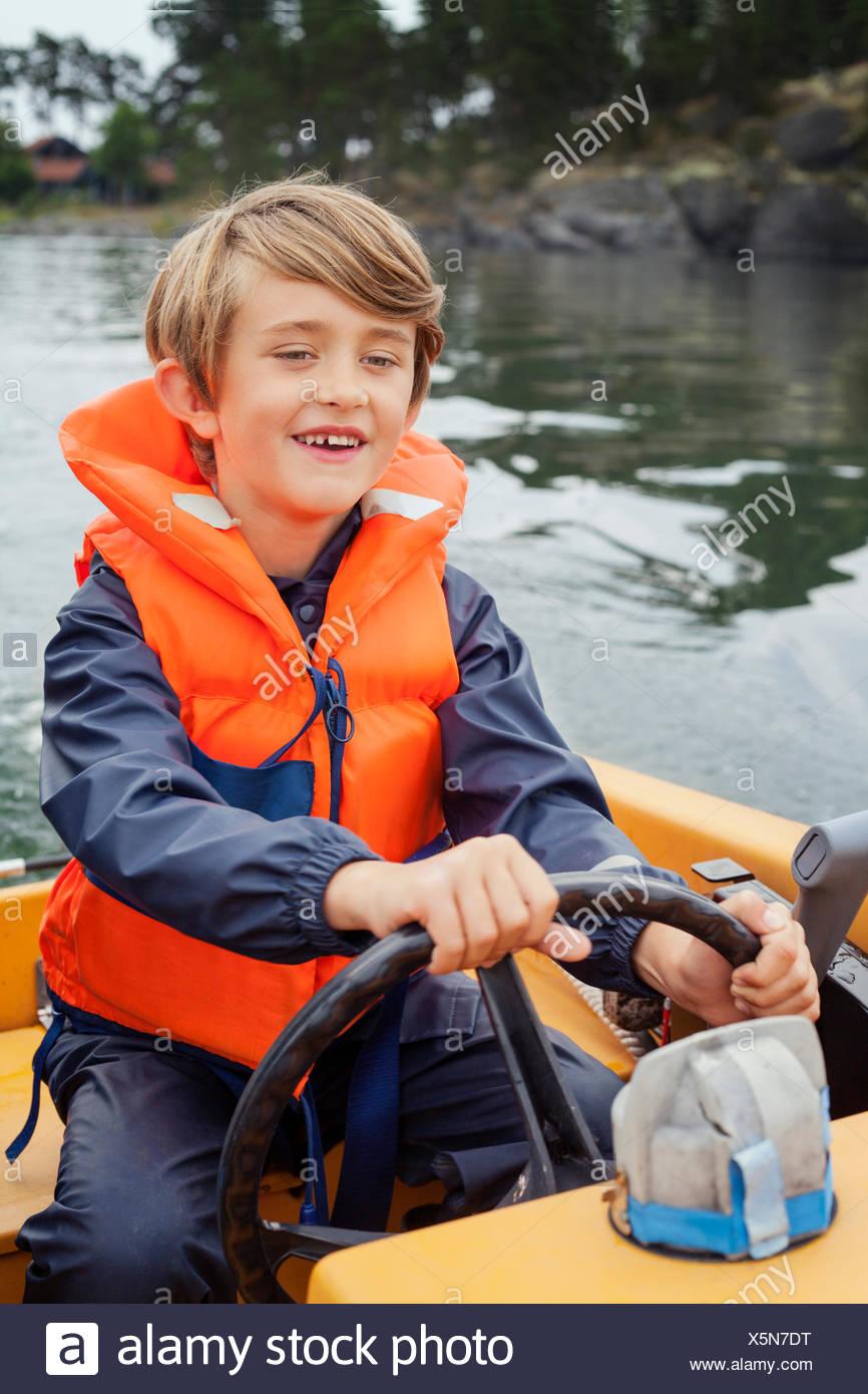 Sweden, Uppland, Runmaro, Barrskar, Boy (6-7) steering motorboat - Stock Image