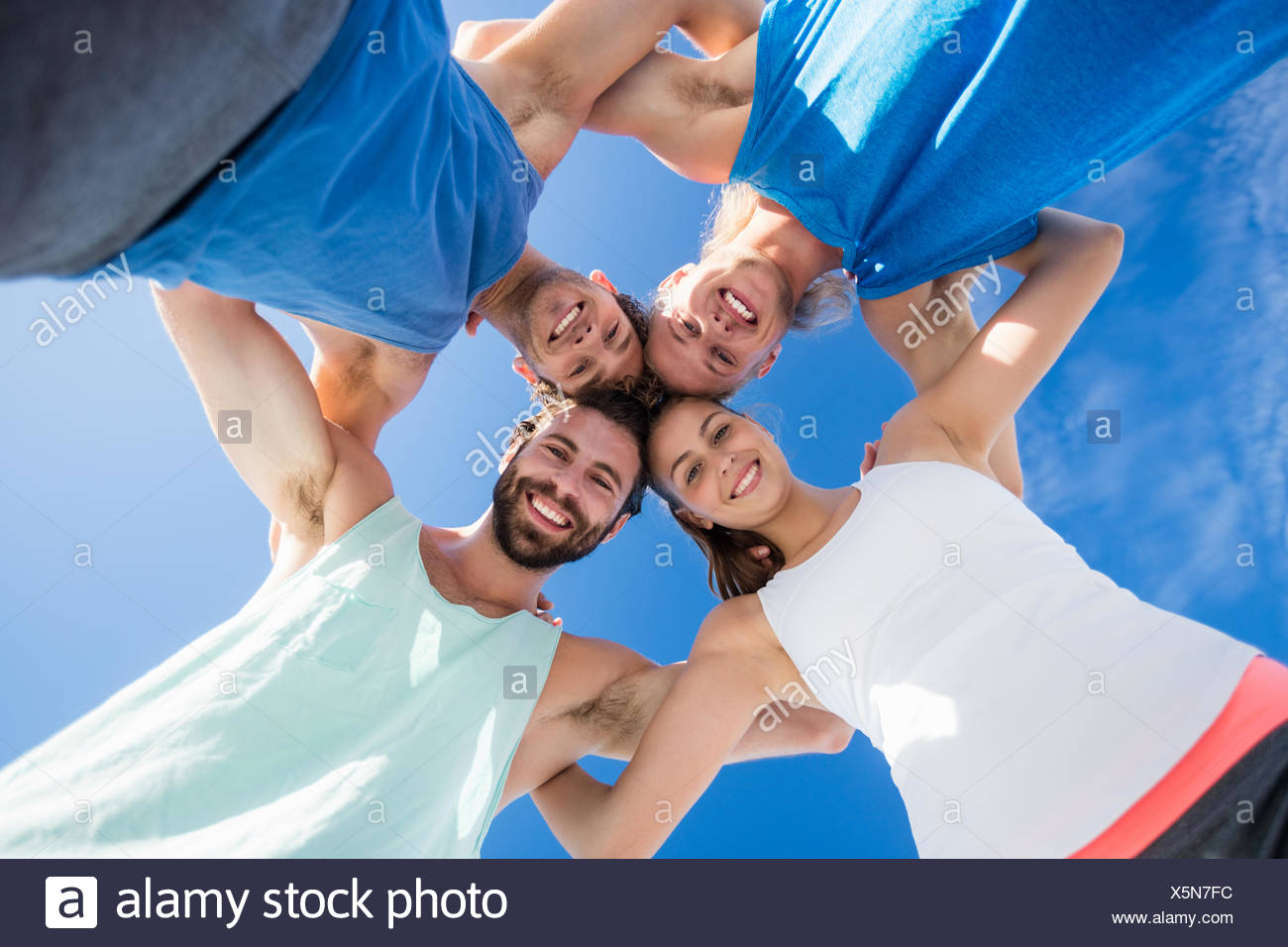 Friends putting their heads in a cirlce - Stock Image