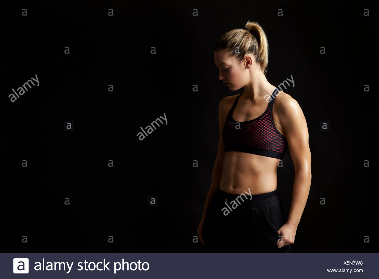Portrait of a blonde woman in sports clothing looking down Stock Photo