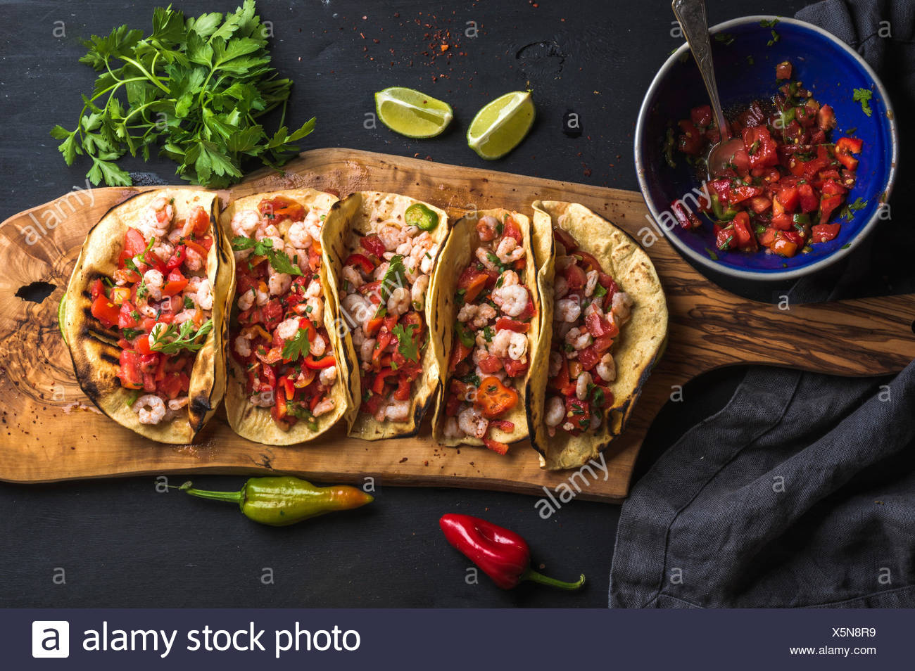 Shrimp tacos with homemade salsa sauce, limes and parsley on wooden board over dark background. Top view. Mexican cuisine - Stock Image