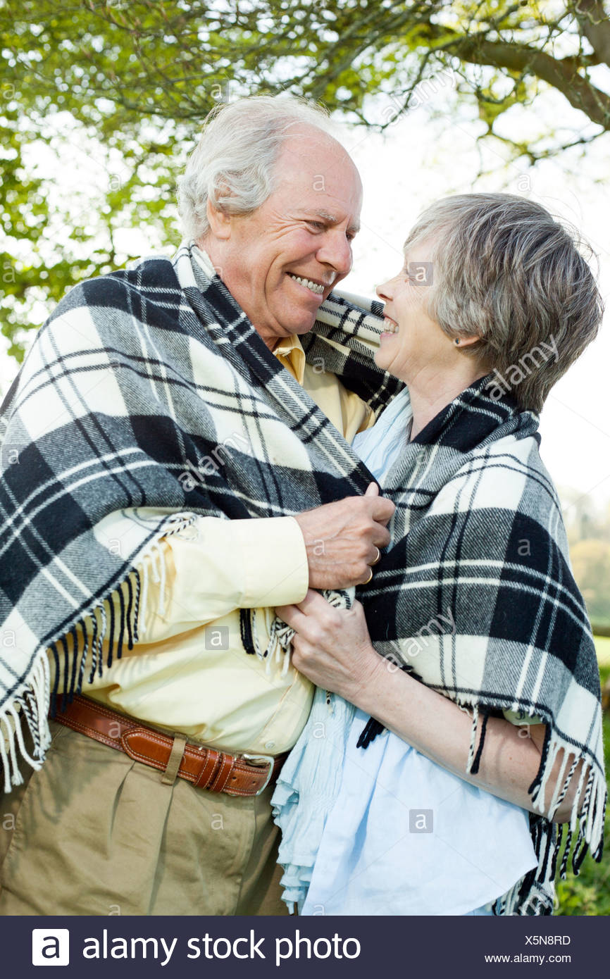 Senior couple wrapped in shawl together - Stock Image
