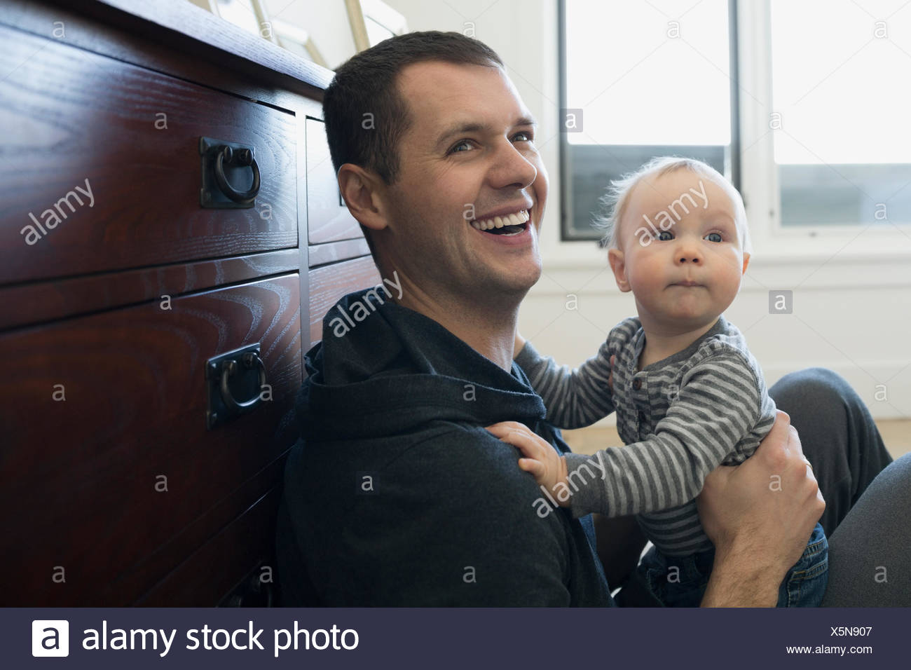 Laughing father holding baby son - Stock Image