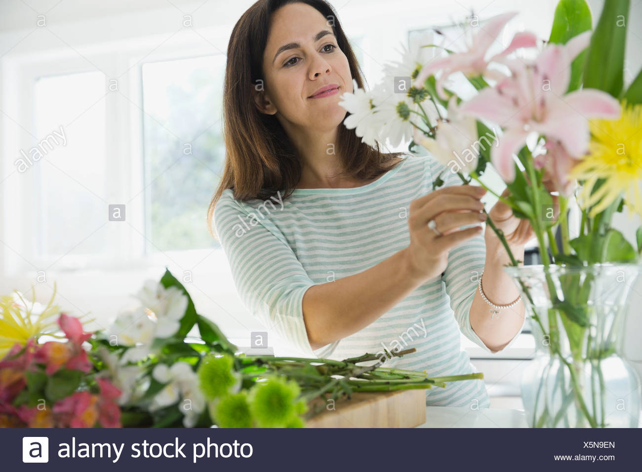 Woman arranging flowers in vase at home - Stock Image
