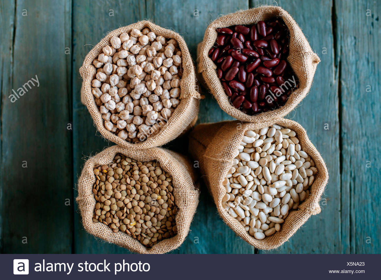 Four sacks of dried brown lentils, chickpeas and red and white beans on wood Stock Photo