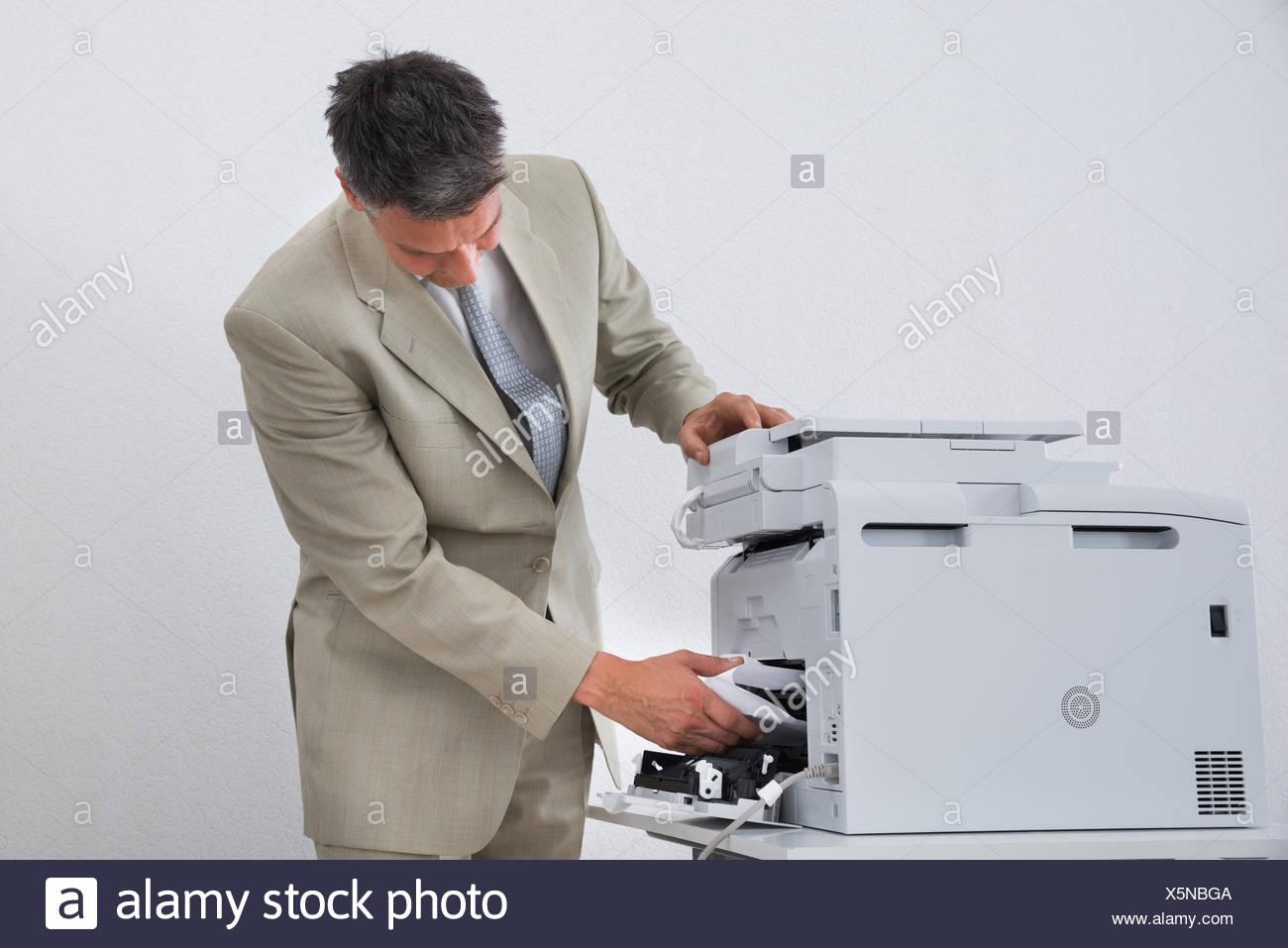 Businessman Removing Paper Stuck In Printer - Stock Image