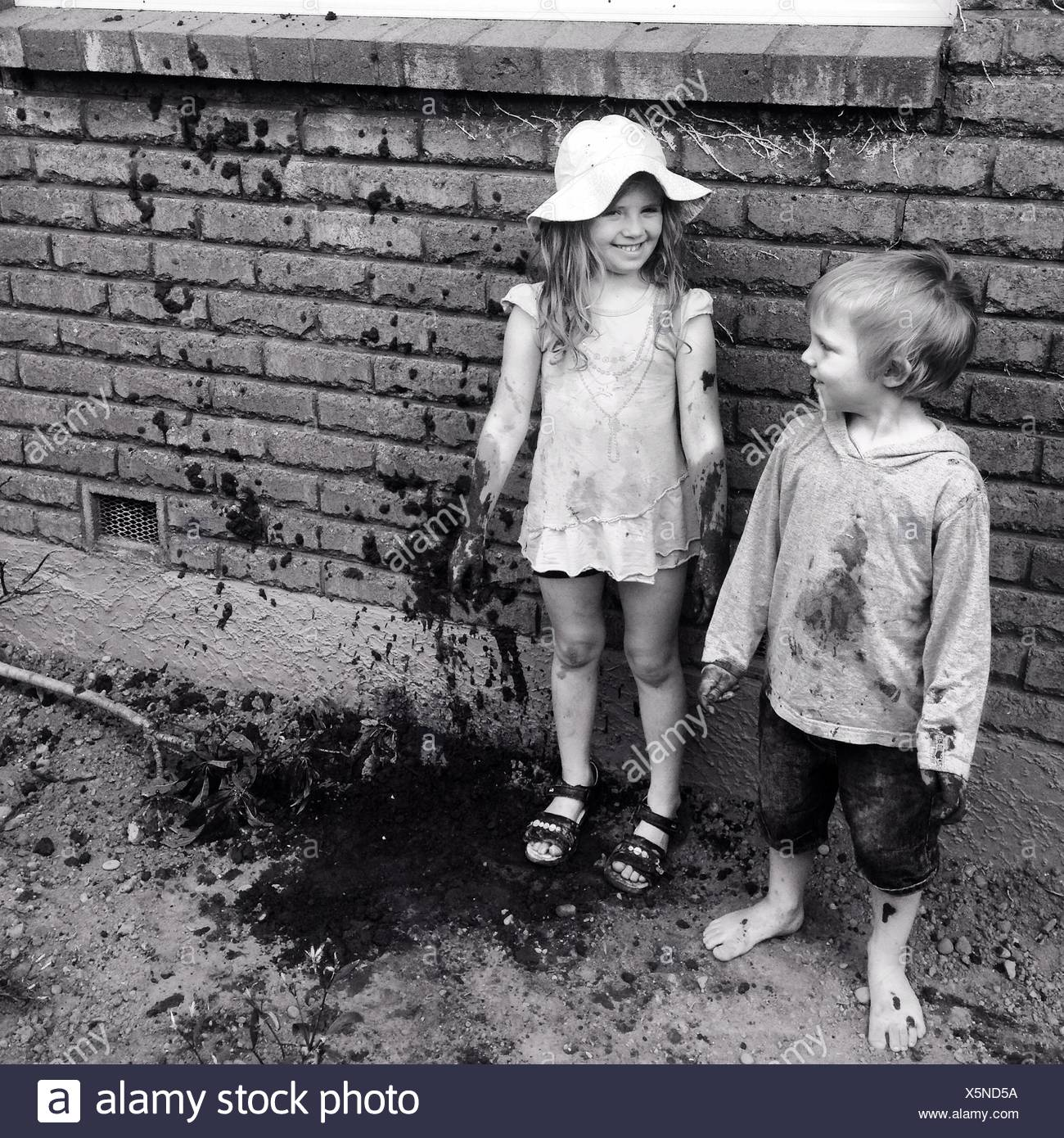 Boy And Girl Playing With Mud - Stock Image