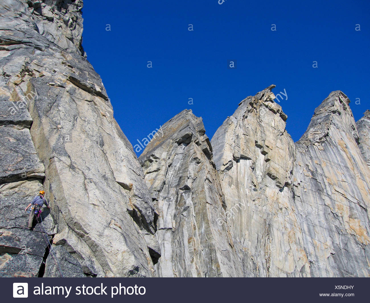 A rock climber begins the fifth pitch of The Pillared Arete on Caliban East, Arrigetch Peaks, Brooks Range, Alaska - Stock Image