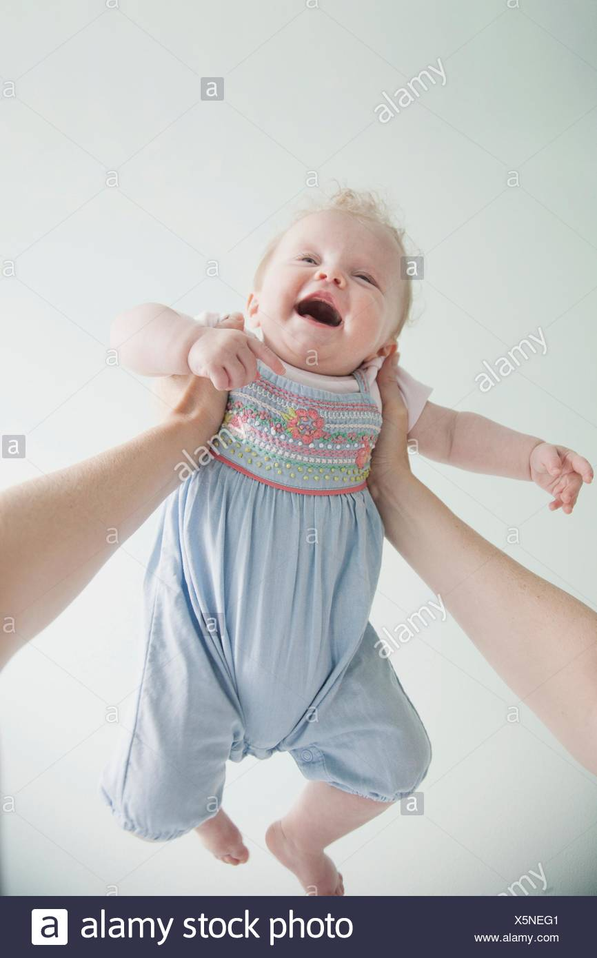 Mother holding baby daughter in air - Stock Image