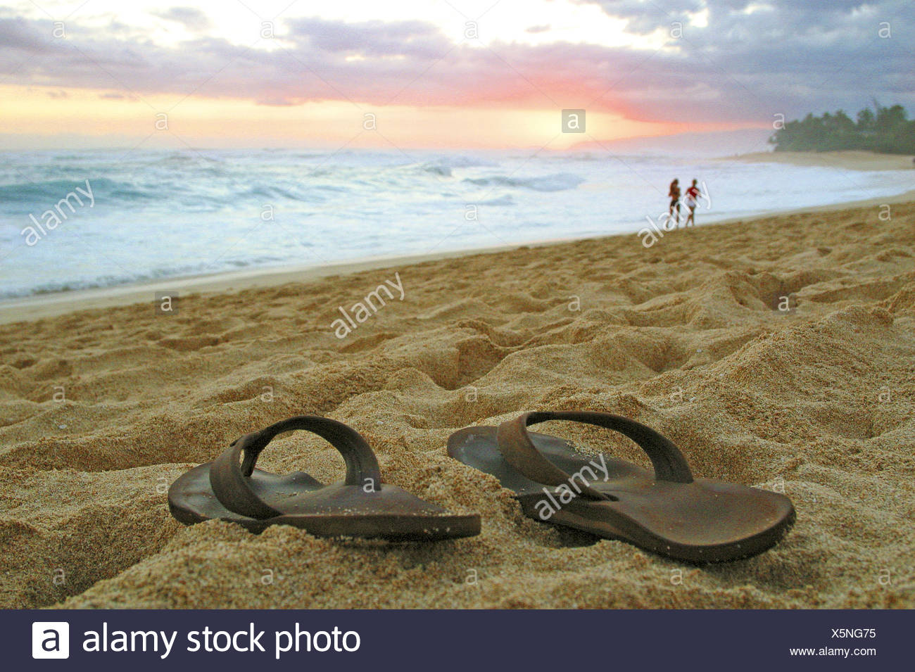 sun sets over sandy beach on Oahu's northshore as this slipper owner opts to go barefoot - Stock Image
