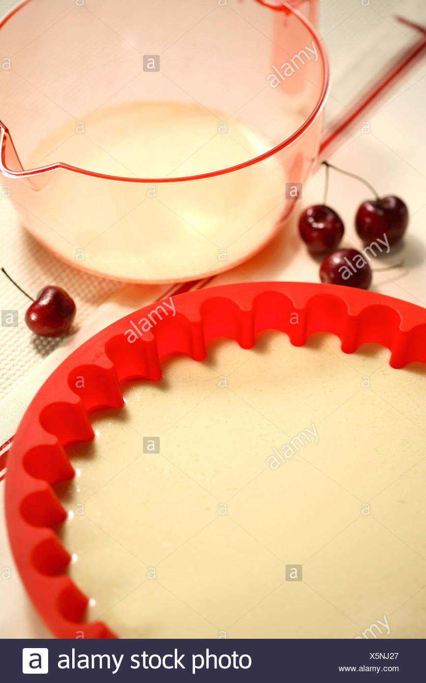 Pouring the Clafoutis batter in a mould - Stock Image