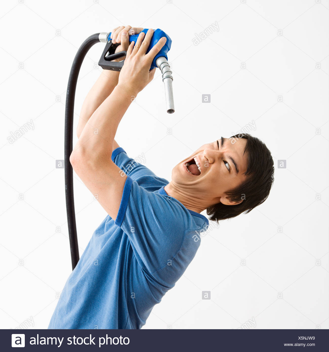 Asian young man fighting with gasoline pump nozzle - Stock Image