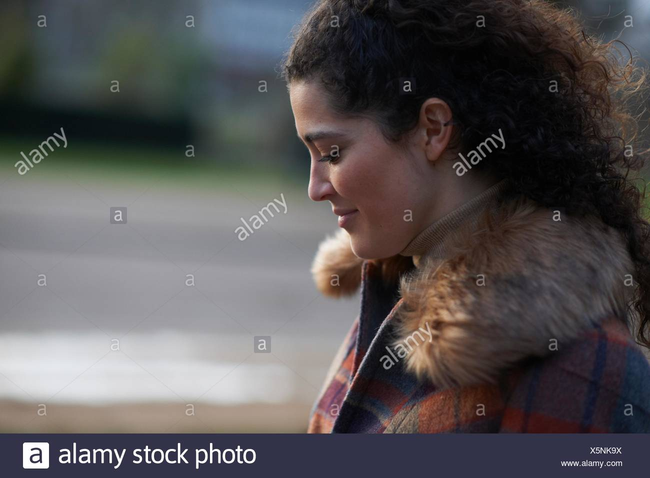 Side view of curly haired woman wearing tartan fur trim coat looking down smiling - Stock Image
