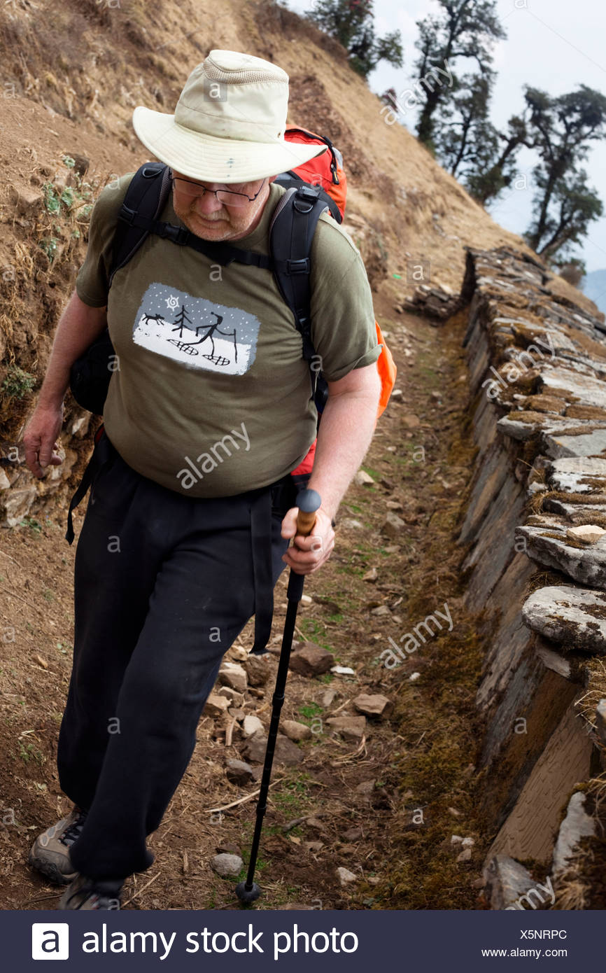 An older male trekker passing a Buddhist prayer wall in Nepal - Stock Image