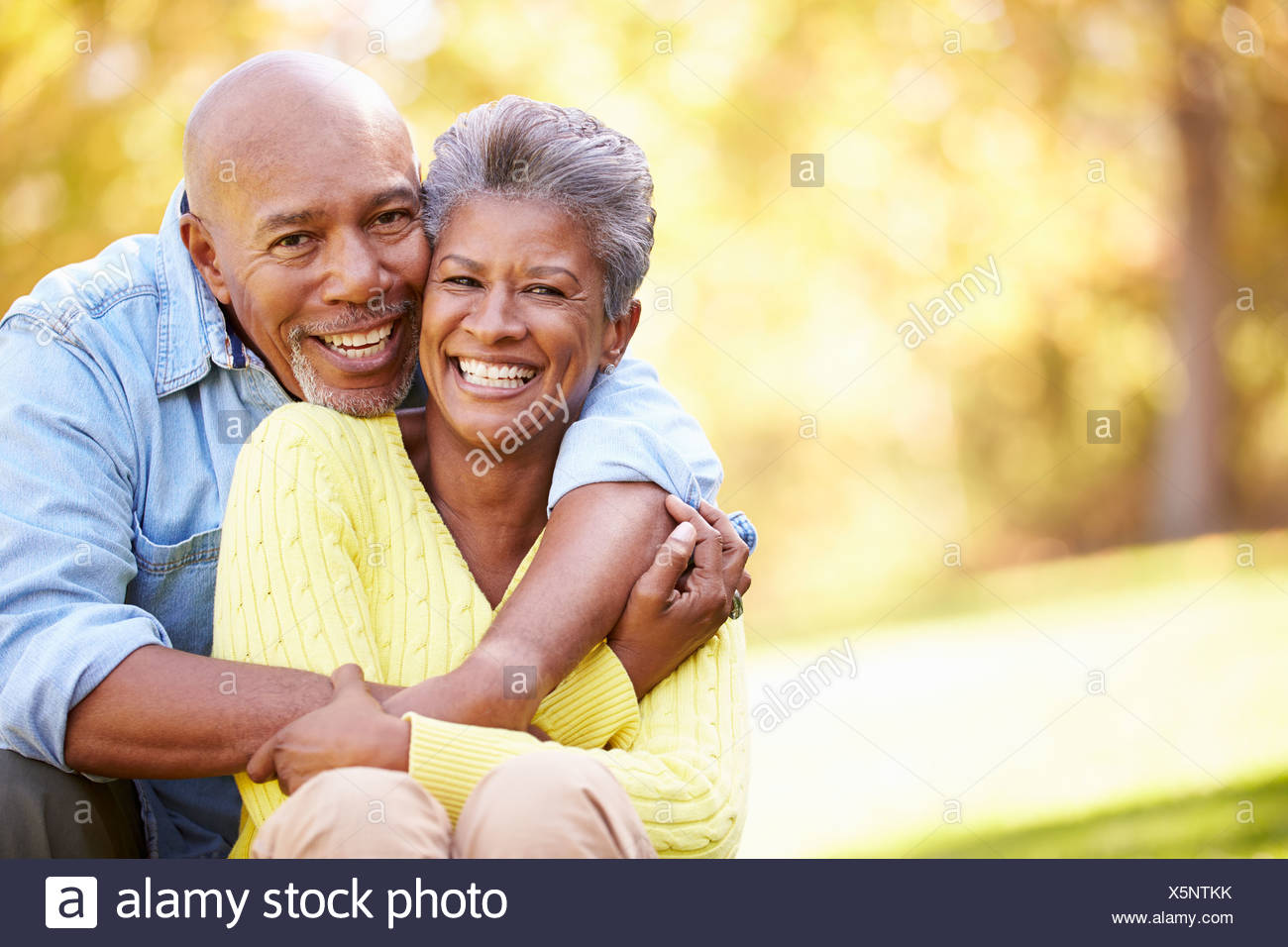 Senior Couple Relaxing In Autumn Landscape - Stock Image
