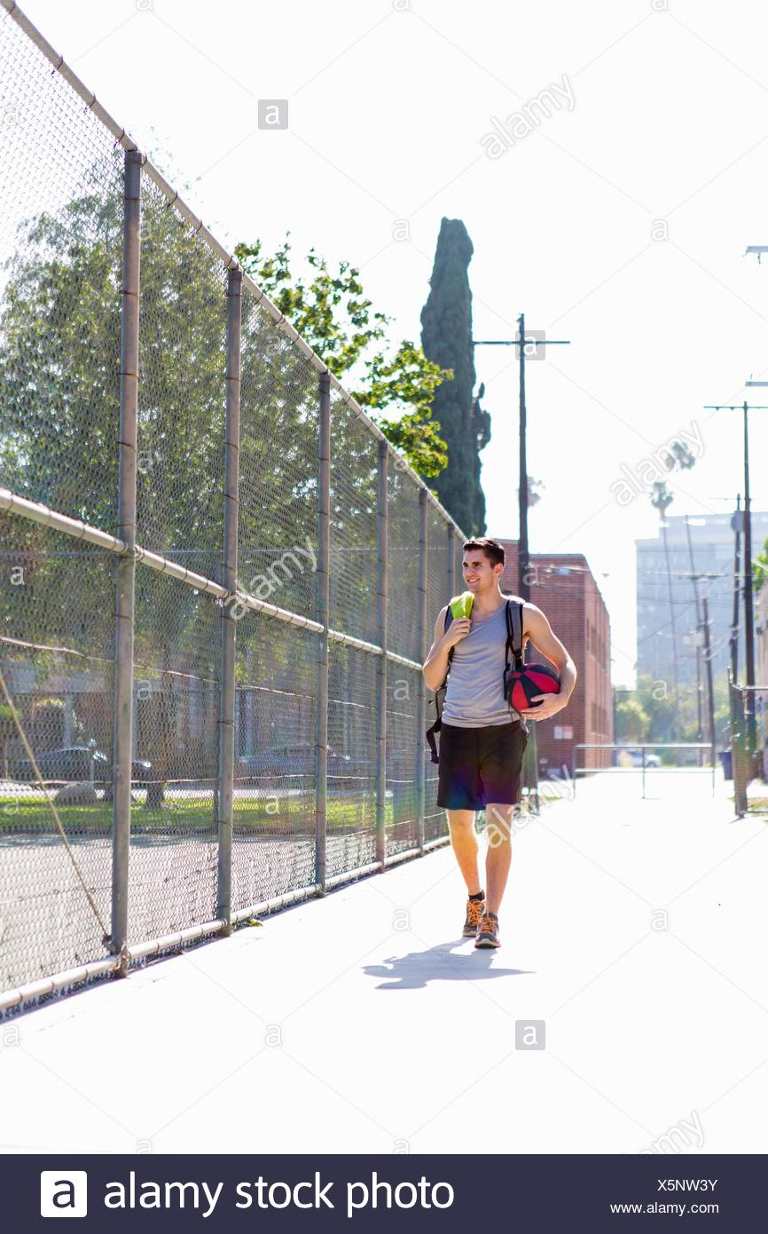 Young male basketball player walking to basketball practice - Stock Image