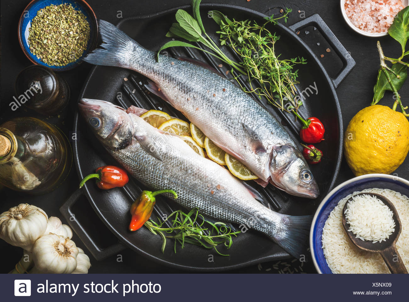 Ingredients for cookig healthy fish dinner. Raw uncooked seabass fish with rice, lemon, herbs and spices on black grilling iron - Stock Image