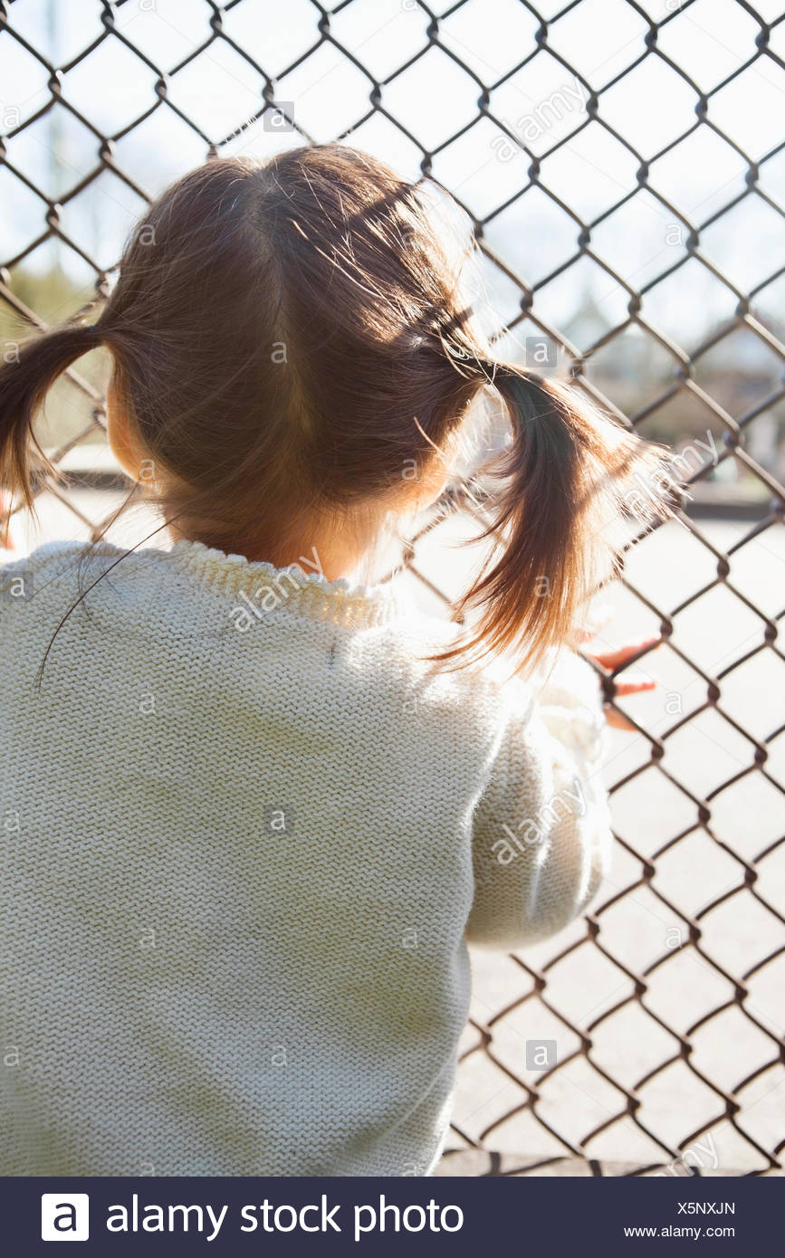 Girl standing at chain link fence - Stock Image