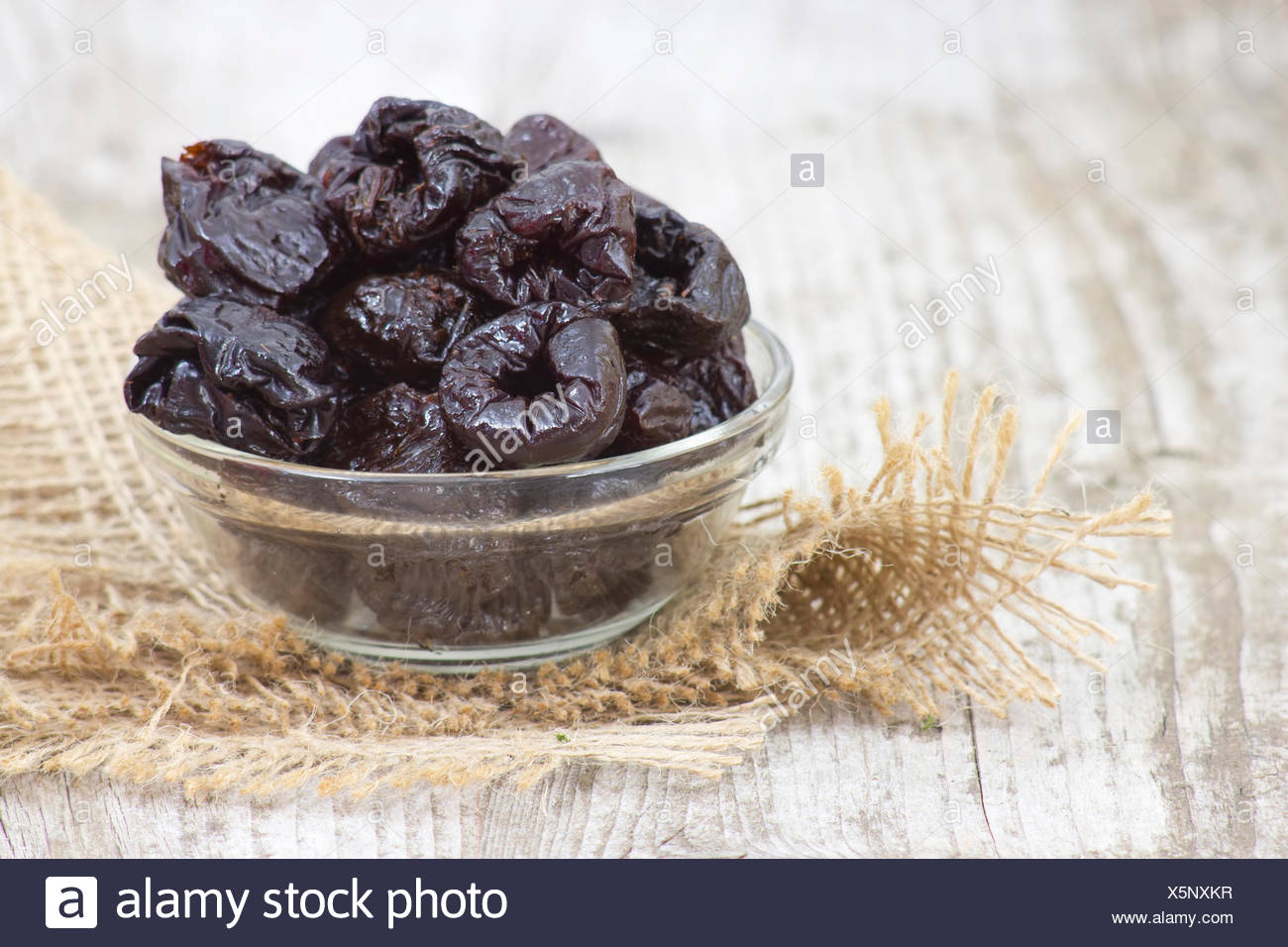 bowl full of dried plums - Stock Image