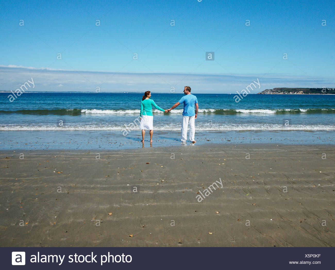 Couple standing at the beach, holding hands, rear view - Stock Image
