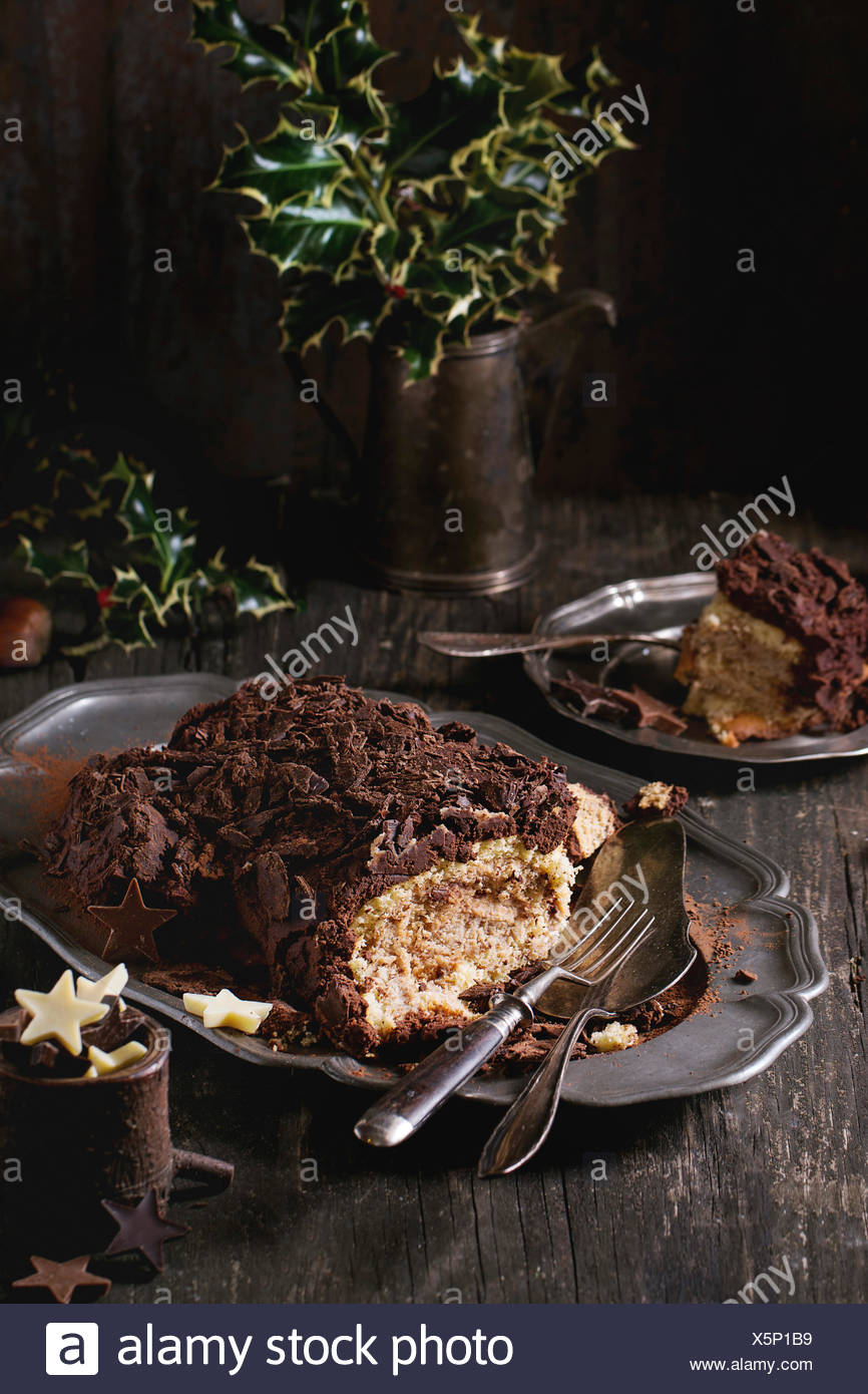 Sliced homemade Christmas chocolate yule log with chestnuts cream on vintage plate with forks,  chocolate stars and holly branch - Stock Image