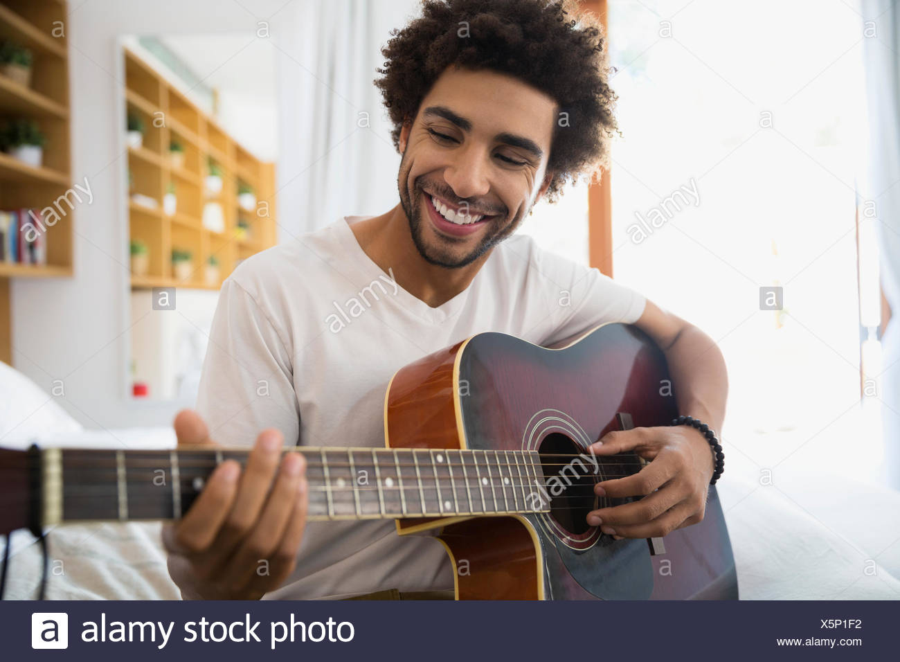 Smiling man playing guitar in bedroom - Stock Photo