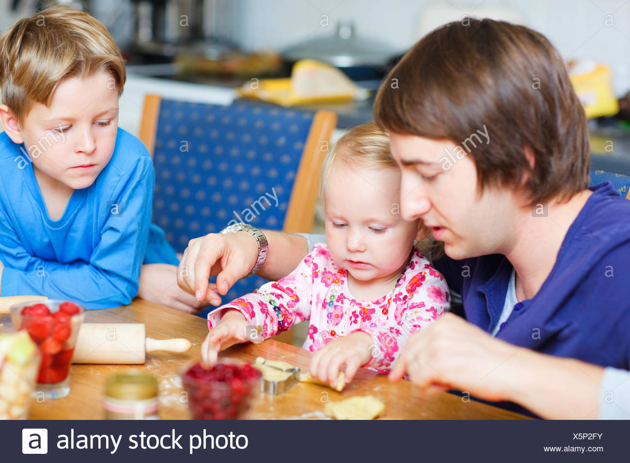 father and his two little children baking biscuits - Stock Image