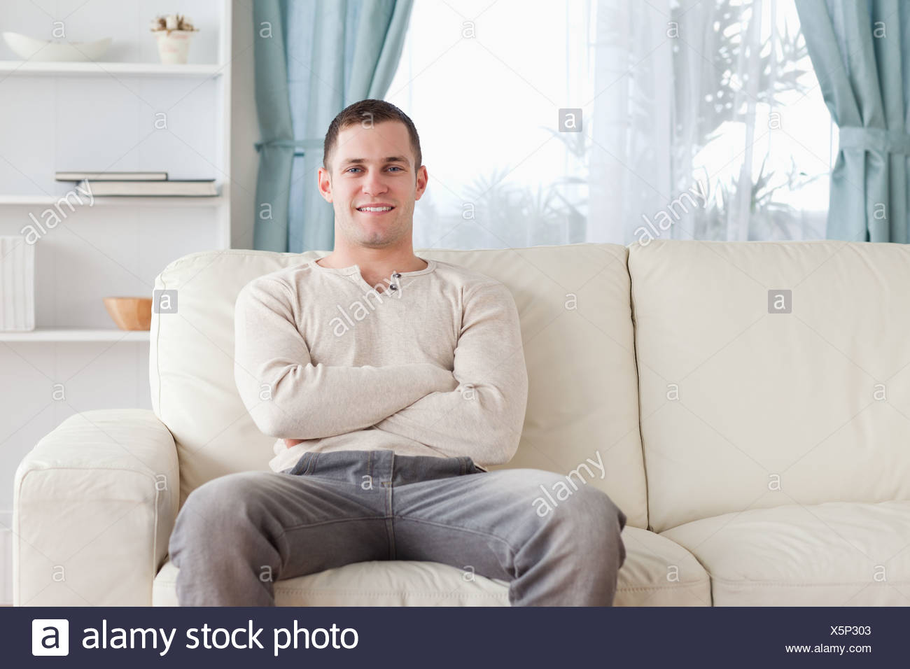 Man sitting on a couch Stock Photo