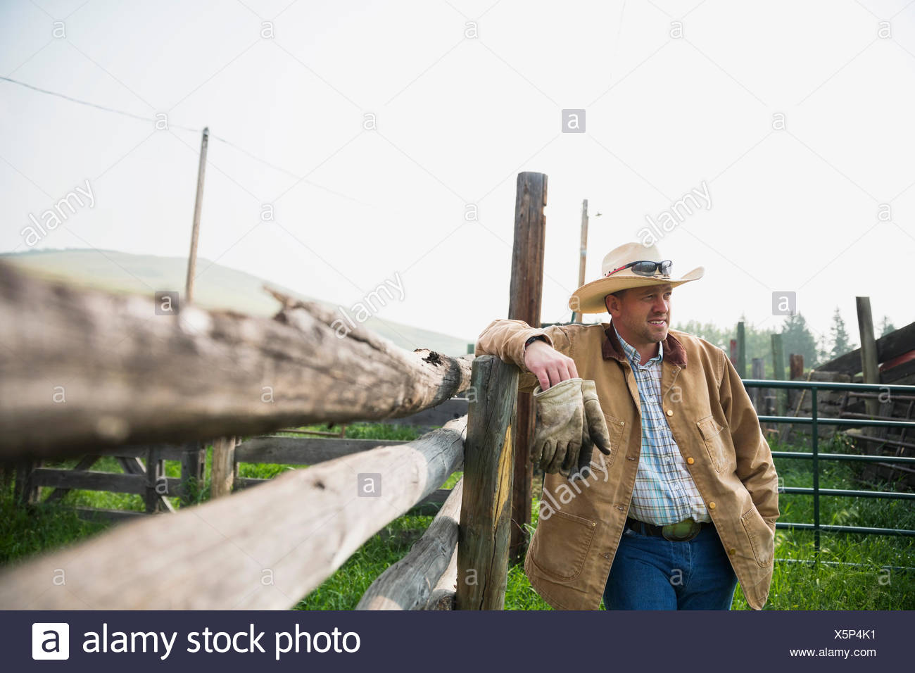 Rancher leaning on pasture fence - Stock Image