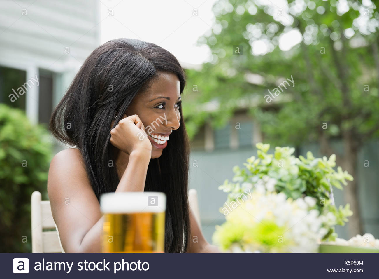 Cheerful woman sitting in back yard looking away - Stock Image