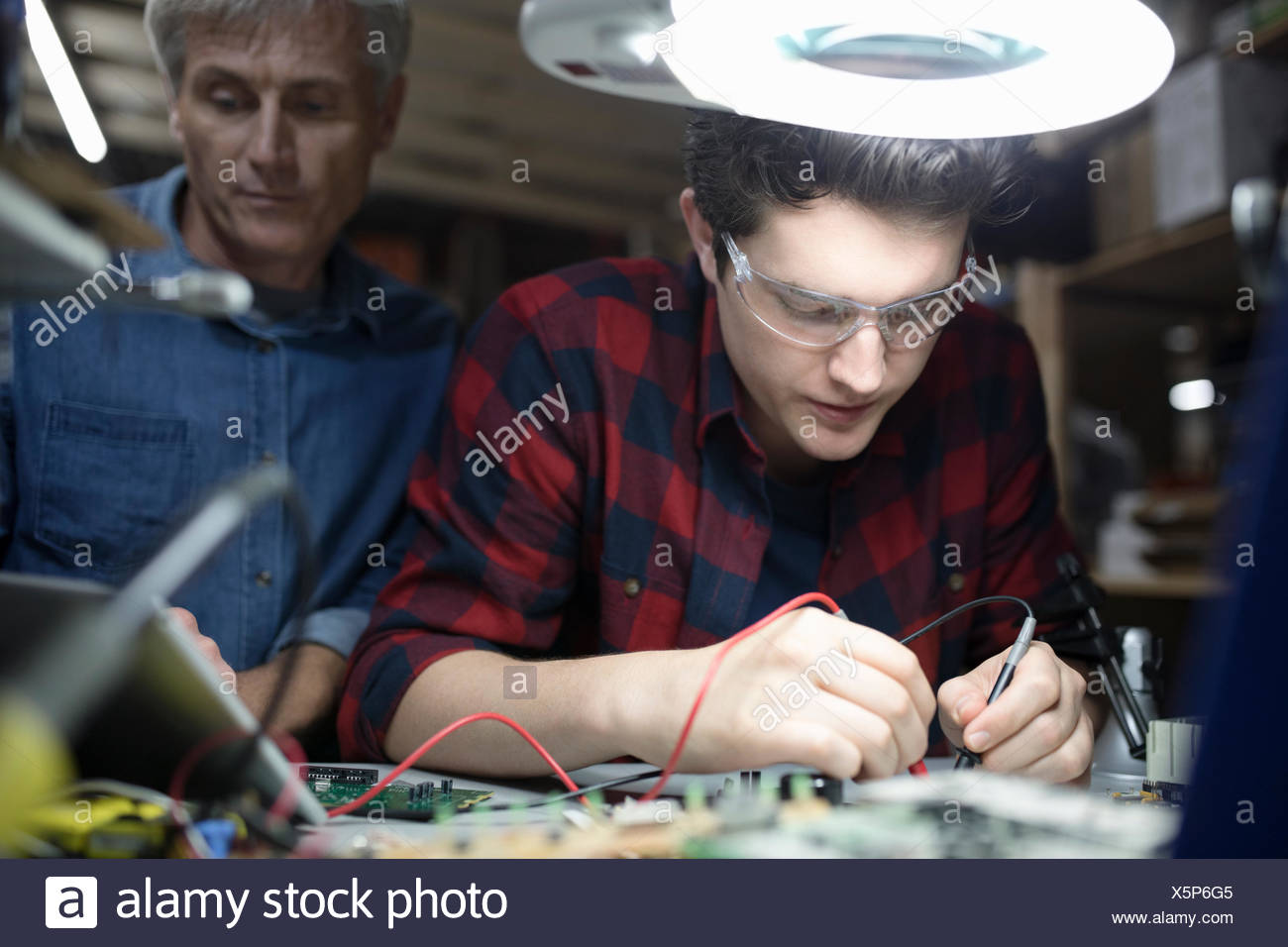 Male engineers using soldering iron on electronics circuit board in workshop - Stock Image