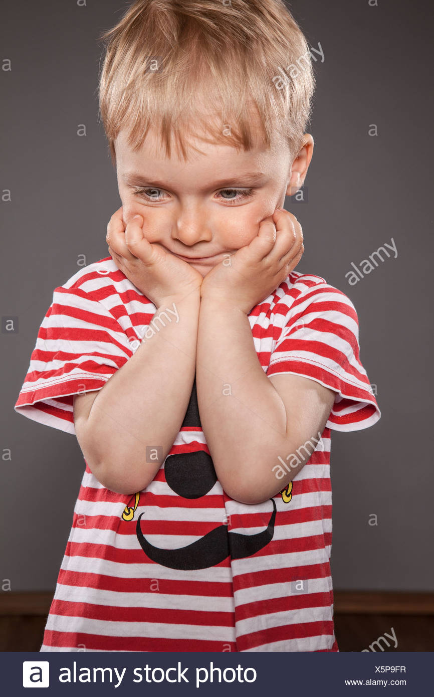 Portrait of little boy holding head in his hands Stock Photo