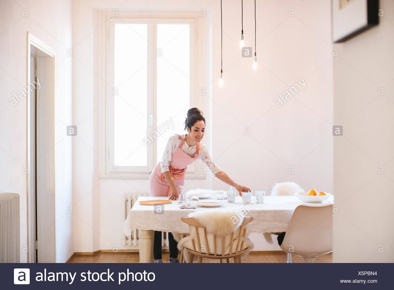 Young housewife wearing apron preparing dining table - Stock Image