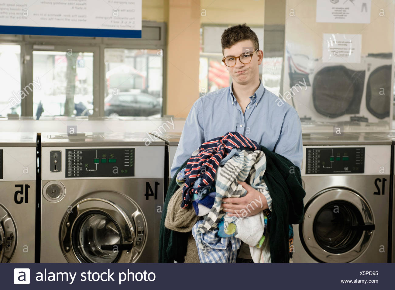 Portrait of young man with laundry - Stock Image