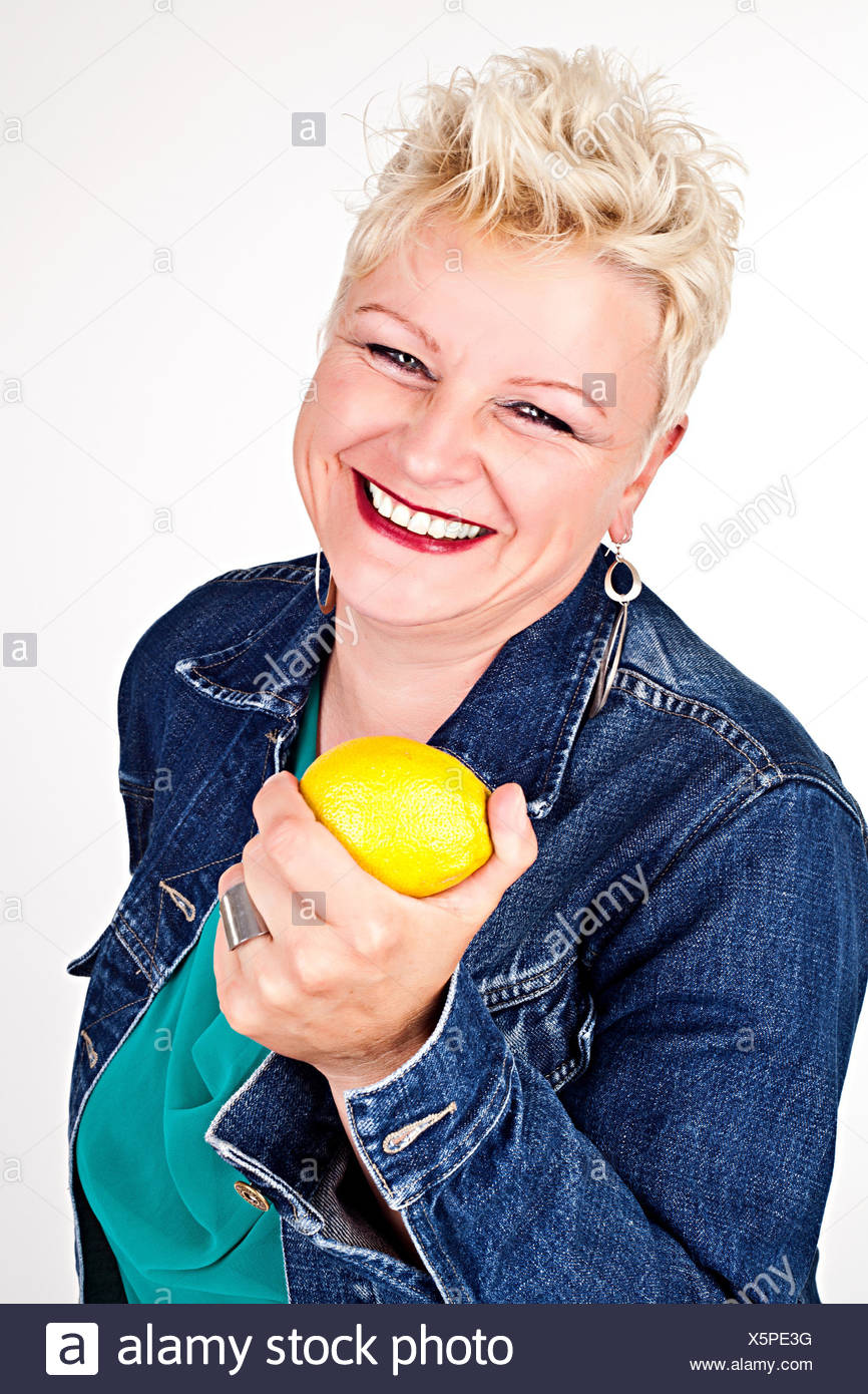 portrait of middelaged beautiful woman eating fresh lemon Stock Photo